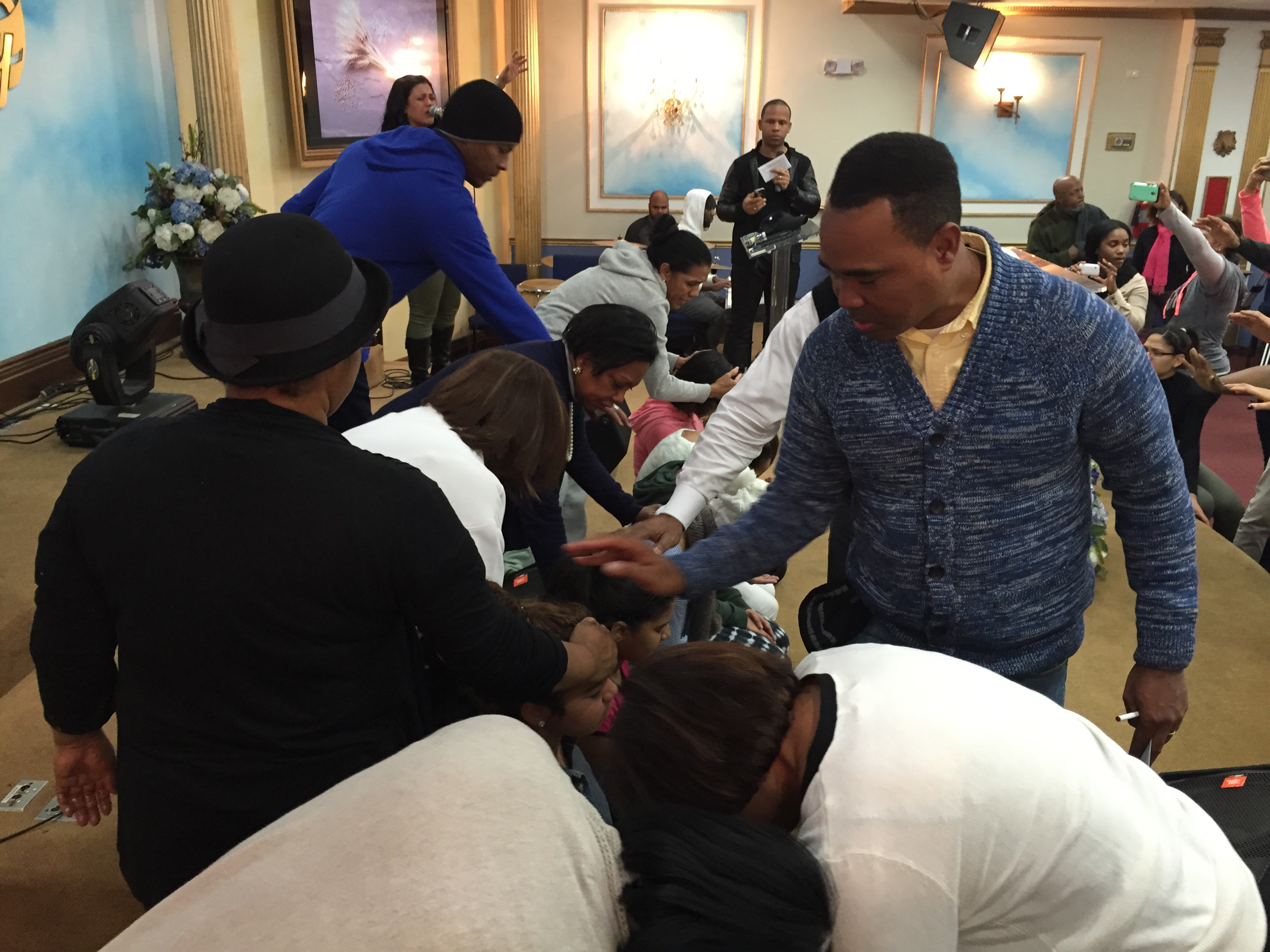 The pastoral team laying hands and anointing new leaders